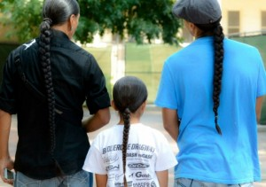 American Indian men and boy with long hair.